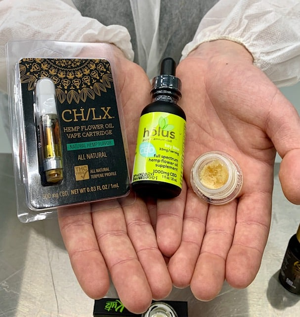 CBD vape cartridge, tincture and isolate held in hands