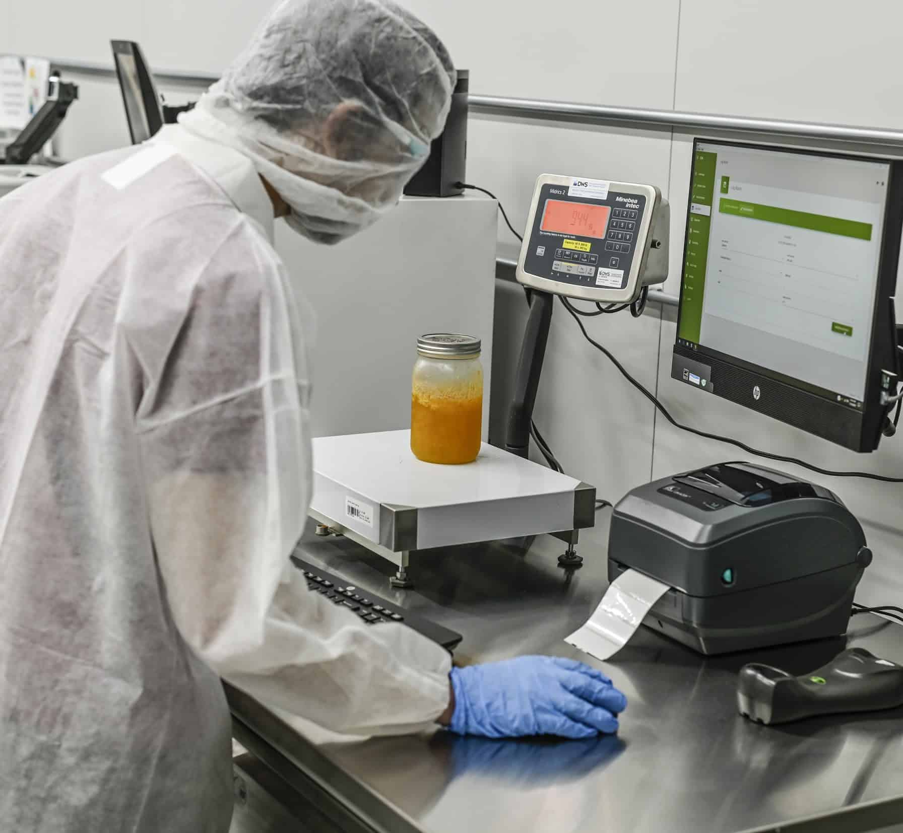 Personnel weighing distillate with igwLAB