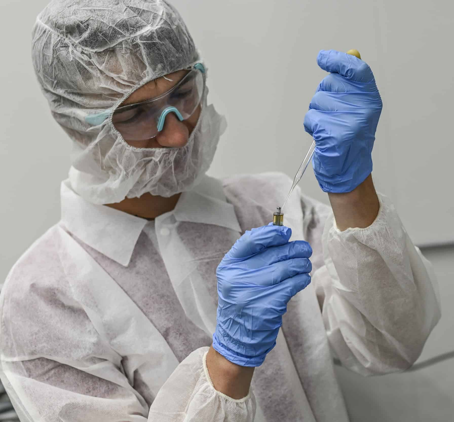 man in lab coat checking solution